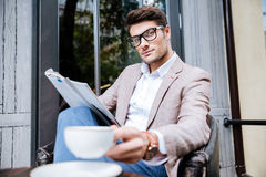 Confident relaxed young man reading magazine in outdoor cafe Stock Photo