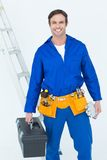 Confident repairman carrying tool box Stock Image