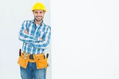 Confident repairman leaning on blank billboard Stock Image