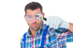 Confident repairman looking through wrench Stock Images