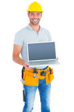 Confident repairman showing laptop Royalty Free Stock Photography