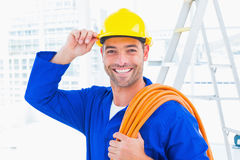 Confident repairman wearing hard hat while holding wire roll Stock Image