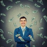 Confident rich businessman. Confident, rich businessman smiling with crossed hands and a and a rain of dollars falling down. Business planning and success stock photos