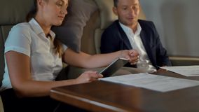 Confident rich colleagues discussing about business during first class flight stock video footage