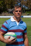 Confident rugby player holding ball at field Stock Images