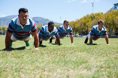 Confident rugby players doing push up at field. On sunny day Stock Photo