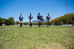 Confident rugby team running at field. On sunny day Royalty Free Stock Photo