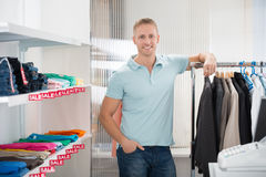 Confident Salesman Leaning On Rack In Clothing Store Royalty Free Stock Photography