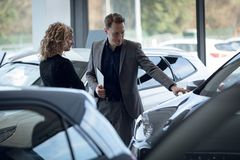 Confident salesman showing car to customer in showroom. Confident salesman showing car to female customer while working standing in showroom royalty free stock photo