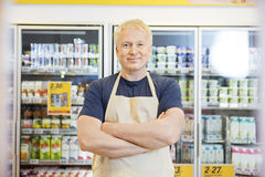Confident Salesman Standing With Arms Crossed In Grocery Store Royalty Free Stock Photography