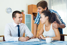 Confident salesman and young spouses discussing contract Royalty Free Stock Photography