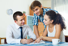 Confident salesman and young spouses discussing contract. Confident salesman and young smiling european spouses discussing contract at home royalty free stock images