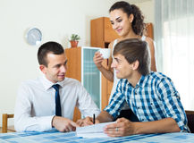 Confident salesman and young spouses discussing contract Stock Photo