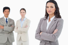 Confident saleswoman with arms folded and colleagues behind her Royalty Free Stock Photos
