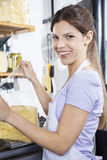 Confident Saleswoman Packing Cheese At Store Royalty Free Stock Photo