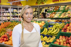 Confident Saleswoman Smiling By Fruit Crates In Supermarket Royalty Free Stock Image