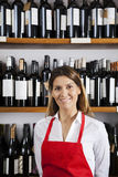 Confident Saleswoman Standing Against Shelves In Wine Shop Royalty Free Stock Image