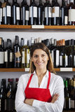 Confident Saleswoman Standing Against Shelves In Wine Shop Stock Images