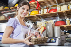 Confident Saleswoman Weighing Cheese At Grocery Store Royalty Free Stock Images