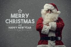 Confident Santa Claus and Christmas wishes. Confident Santa Claus posing with arms crossed and Christmas wishes, snow falling on the background stock photo