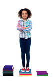 Confident school child standing on books Stock Photo