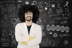 Confident scientist standing with arms crossed. Portrait of confident male scientist standing with crossed arms and looking at camera. Shot with doodles Stock Photography