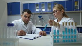 Confident scientists examining solution in lab. Confident charming female supervisor in eyeglasses holding test tube with blue liquid while her male mixed race stock video footage