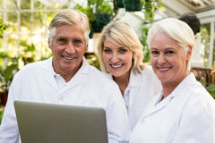 Confident scientists with laptop at greenhouse. Portrait of confident scientists with laptop at greenhouse Royalty Free Stock Images