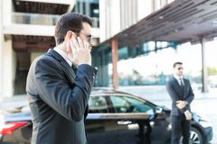 Bodyguard Getting Information About Arrival Of Boss. Confident secret service agent listening to updates from security earpiece while waiting by car stock photos