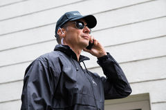 Confident Security Guard Listening To Earpiece Against Building. Confident mature security guard listening to earpiece against building Royalty Free Stock Image