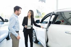 Confident Seller Displaying Features Of Car Proudly. Pretty salesperson opening royal car door for client to inspect its features at showroom stock photography