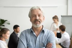 Confident senior businessman leader looking at camera, team at b. Confident senior businessman leader looking at camera with team at background, smiling aged Royalty Free Stock Images