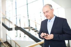 Senior Businessman Texting On Smartphone. Confident senior businessman texting on smartphone in office Royalty Free Stock Photos