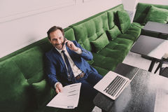 Confident senior businessman using phone for communication. Successful business deal. Top view of excited middle-aged man is talking about business with his Royalty Free Stock Photography