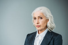 Confident senior businesswoman in suit  on grey Royalty Free Stock Image