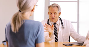 Confident Senior doctor discussing surgery procedure with elderly woman patient Stock Image