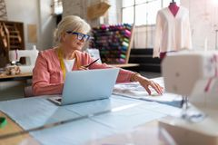 Confident senior fashion designer in her workshop Stock Image