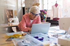 Confident senior fashion designer in her workshop Royalty Free Stock Image