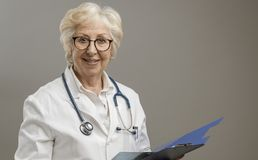 Confident senior female doctor posing and smiling. She is holding a clipboard with medical records, medicine and healthcare concept stock photos