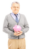 Confident senior gentleman holding a piggy bank and looking at c Stock Images