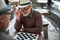 Confident senior male pensioner enjoying draughts game Royalty Free Stock Photo