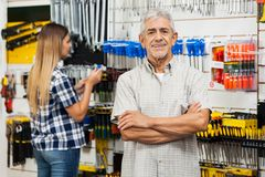 Confident Senior Man With Arms Crossed In Hardware Stock Photos