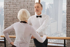 Confident senior man dancing with aging woman in the ballroom. With all my enthusiasm . Optimistic charming happy aging men tangoing with age women in the dance stock image