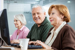 Confident Senior Man With Female Friends In Computer Class. Portrait of confident senior men sitting in computer class with female friends at desk Royalty Free Stock Photography