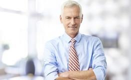 A confident senior man portrait. A confident senior man wearing shirt with rolled up sleeves while standing in the office with arms crossed Royalty Free Stock Photo