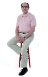 Confident senior man resting on stool. Confident senior man looking at you as he rests on stool, studio shot Royalty Free Stock Photos