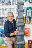 Confident Senior Man Stacking Toolboxes In Store Royalty Free Stock Photos