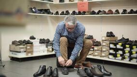 Confident senior man trying on one of many shoes in shop. Portrait of male Caucasian retiree selecting boots in store on