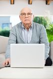 Confident Senior Man Using Laptop At Nursing Home Stock Images