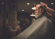 Confident senior man visiting hairstylist in barber shop. Stock Photo